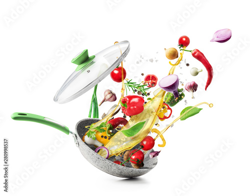 Fototapeta Cooking concept. Vegetables are flying out of the pan isolated on white background. Healthy food. obraz