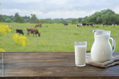 Leinwand Poster Fresh milk in glass on dark wooden table and blurred landscape with cow on meadow