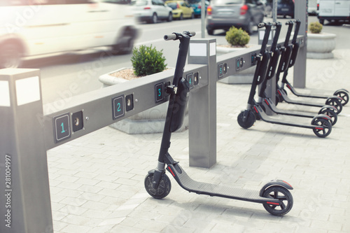 Electric schooters parked on the sidewalk avaliable for rent on the city street. Urban life concept. Eco-friendly transportation. - 281004997