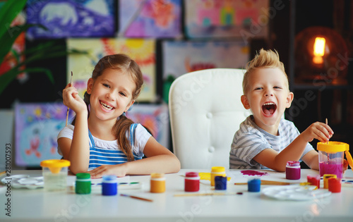 Foto auf AluDibond Akt funny children girl and boy draws laughing with paint.