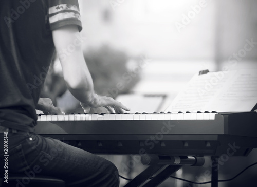 Fototapety, obrazy: Black and white image, where a skilled pianist, dressed in a t-shirt and jeans, plays a beautiful melody on the synthesizer at a concert