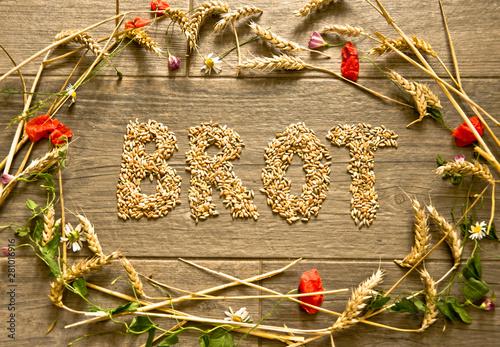 """Obraz na plátně Aus Korn in einem Erntekranz gelegtes Wort """"Brot"""" zum Thema Erntedankfest"""