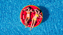 Aerial View Of Two Women Floating On Inflatable Mattresses Relaxing In The Swimming Pool. Summer Time
