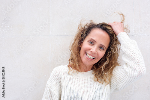 canvas print motiv - mimagephotos : Close up happy middle age woman laughing with hand in hair