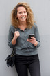 canvas print picture middle age woman smiling with mobile phone by gray background