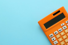 Orange Calculator On A Bright Blue Paper Background. Office Supplies. Education. Back To School. Top View. Place For Text.