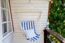 Blue And White Striped Pattern String And Cotton Hammock Hanging Chair, White Painted Wooden Board Background. Relaxing In Countryside Home Garden Balcony Outdoors On Summer Day Concept.