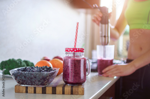Sports healthy woman cooking fresh blueberry smoothie using hand blender at home Canvas Print