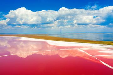 Fototapeta Rzeki i Jeziora Clouds in the sky reflect in pink water of salt lake in aerial view