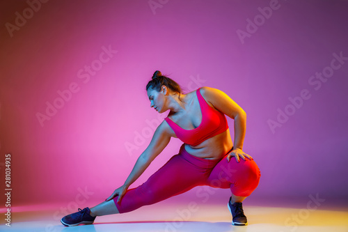 Spoed Foto op Canvas Fitness Young caucasian plus size female model's doing exercises on gradient purple background in neon light. Training in lunges and stratching. Concept of sport, healthy lifestyle, body positive, equality.