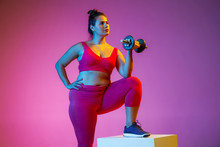 Young Caucasian Plus Size Female Model's Doing Exercises On Gradient Purple Background In Neon Light. Training Upper Body With Weights And Jump Box. Concept Of Sport, Healthy Lifestyle, Body Positive.