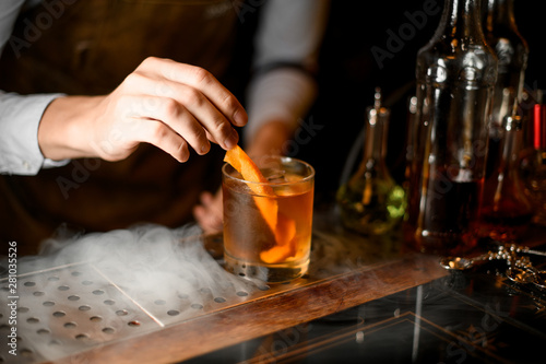 Photo Stands Cocktail Bartender puts orange zest in whiskey glass