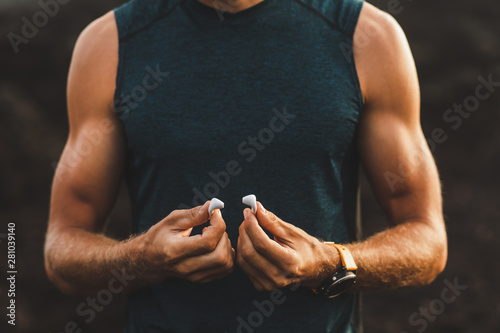 Fotografía Man holding air pods headphones in hands close-up