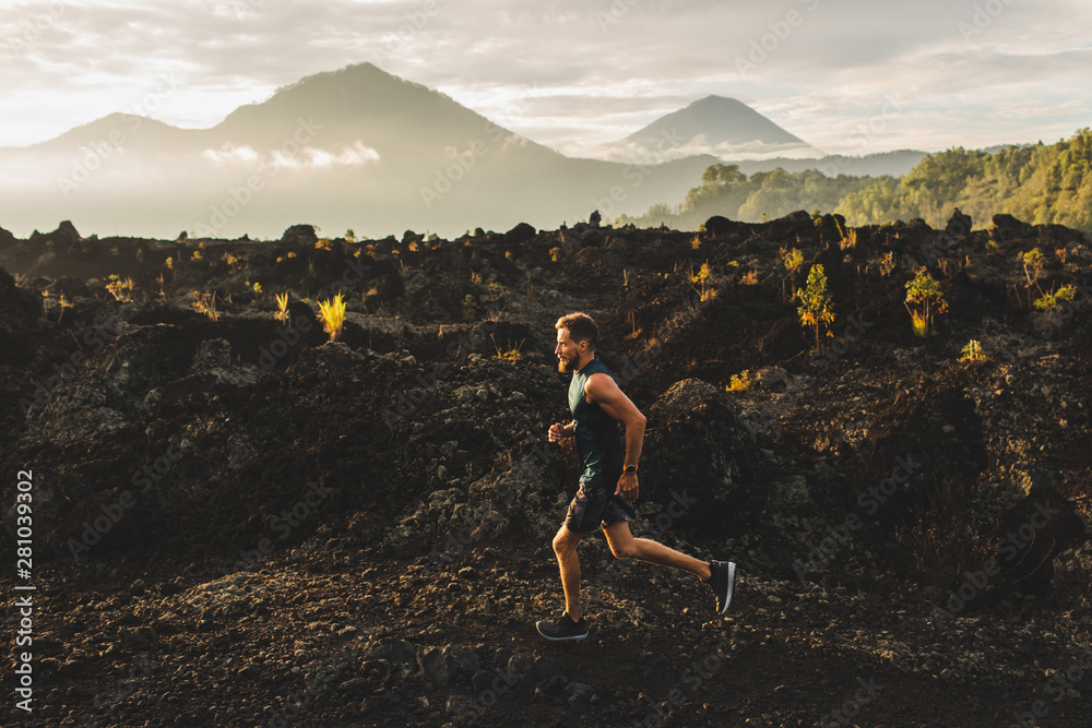 Fototapety, obrazy: Young male athlete trail running in mountains at sunrise. Amazing black lava volcanic landscape of Bali on background. Adventure sport concept.