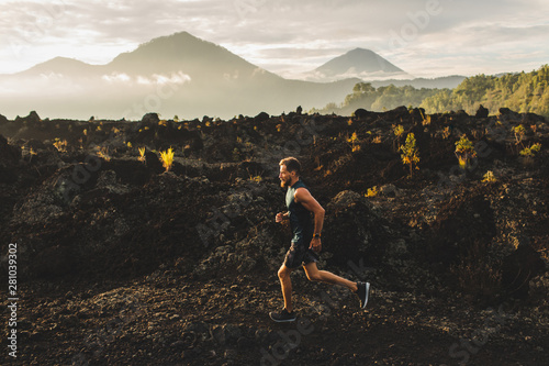 Cuadros en Lienzo  Young male athlete trail running in mountains at sunrise
