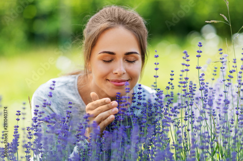 Obraz gardening and people concept - happy young woman smelling lavender flowers at summer garden - fototapety do salonu