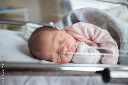 Obraz A newborn baby sleeps in the maternity hospital. Little baby resting after birth - fototapety do salonu