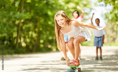 Happy girl is balancing on the skateboard