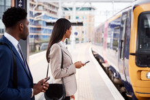 Businessman And Businesswoman Commuting To Work On Railway Platform Waiting For Train