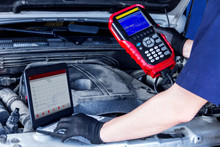 Closeup Laptop Screen With Special Software, Equipment At Vehicle With Open Hood. Repairman Is Conducting Diagnostics And Detecting Problems At Workshop. Mechanic Is Repairing Car At Service Station.
