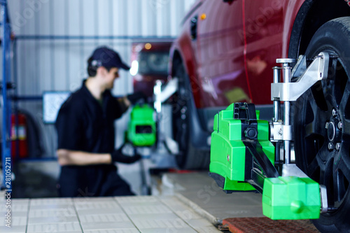 Photo Man mechanic is repairing red car at modern service station