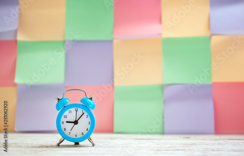 Blue vintage alarm clock on a colorful timetable background