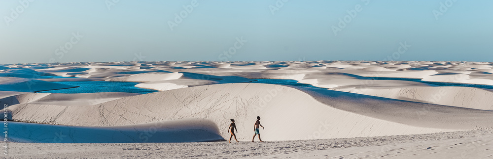 Fototapety, obrazy: travel couple trek across giant sand dunes with lagoons in Lencois Maranhenses, one of the most stunning tourist attracts in North-East Brazil
