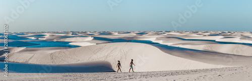 travel couple trek across giant sand dunes with lagoons in Lencois Maranhenses, Fotobehang