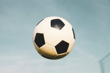 Soccer Ball In Mid Air, Blue Sky Background