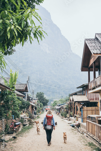 Photo  Young Caucasian blonde woman with backpack walking on the central street of Muan