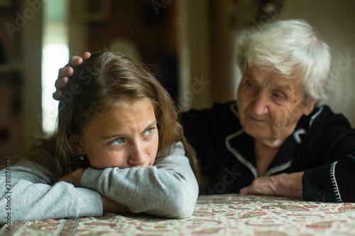 Carta da parati Old lady grandma comforting a crying little girl granddaughter.