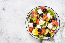 Greek Salad In Black Plate On The Table.