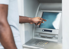 Unrecognizable African Man Using Touch Screen On ATM Outdoor