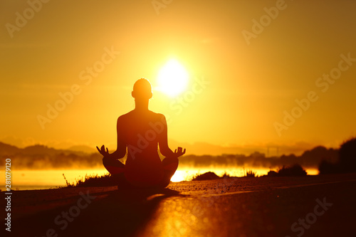 Stampa su Tela  Woman silhouette practicing yoga exercise at sunrise