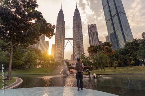 A man backpacker is traveling and sightseeing Landmark twin tower of Kuala Lumpur, Malaysia.