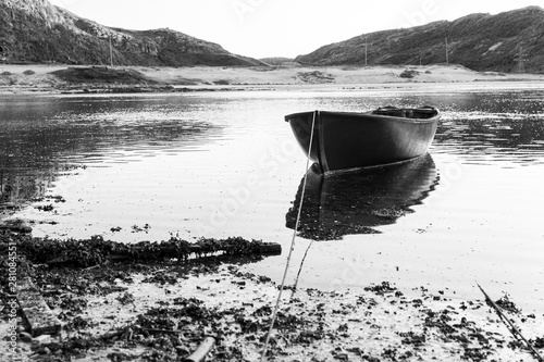 Spoed Foto op Canvas Grijs An old fishing boat is moored on the water. Black and white photo. Dramatic landscape.