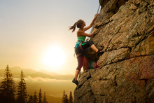 Beautiful Woman Climbing On The Rock At Foggy Sunset In The Mountains. Adventure And Extreme Sport Concept