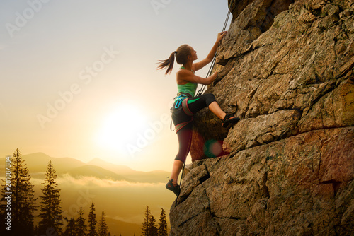 Fototapeta Beautiful Woman Climbing on the Rock at Foggy Sunset in the Mountains. Adventure and Extreme Sport Concept obraz