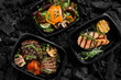 Leinwanddruck Bild - Top view of coal cooked healthy food in take away boxes