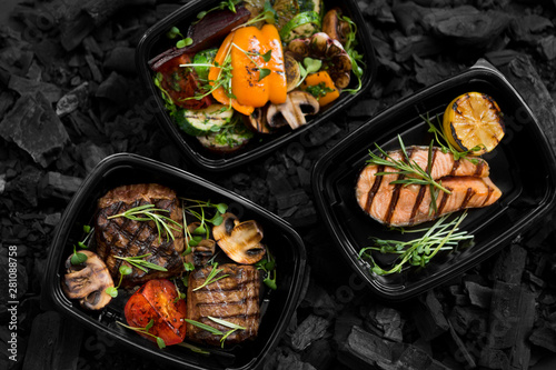 Top view of coal cooked healthy food in take away boxes