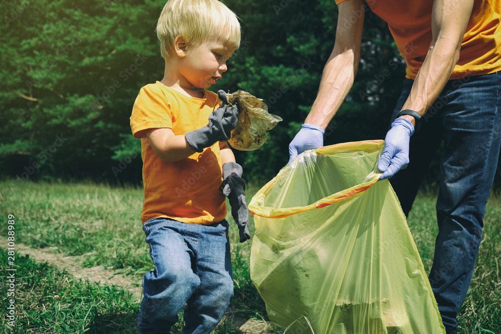 Fototapeta Cute toddler boy and his father collecting garbage in the park. Volunteers family picking up litter in the forest. Environmental protection concept