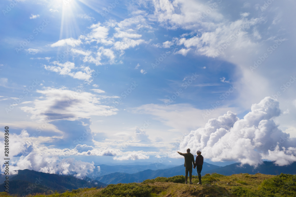 Fototapety, obrazy: The couple standing on a mountain against beautiful clouds