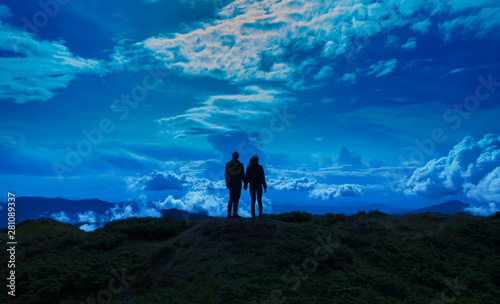 The man and woman standing on the picturesque mountain Wallpaper Mural