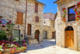 Fototapeta Uliczki - Beautiful stone buildings of the flower filled old town of Assisi, Italy