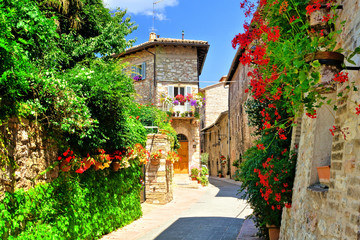 Fototapeta Uliczki Flower filled medieval street in the beautiful old town of Assisi, Italy