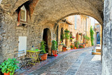Fototapeta Uliczki - Beautiful arched street in the medieval old town of Assisi with flowers and restaurant tables, Italy