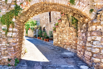 Fototapeta Struktura ściany Medieval buildings of the old town of Assisi through a picturesque stone arch, Italy