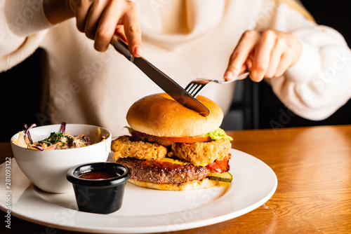 Photo sur Toile Nature .Young woman eating burger in restaurant