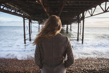 Blond Young Woman Standing Under The Bridge In Coat Looking Towards The Ocean. Moody Landscape. Brighton, West Sussex, England