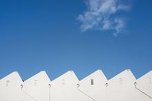 White Factory Sawtooth Roofline Against A Vivid Blue Sky
